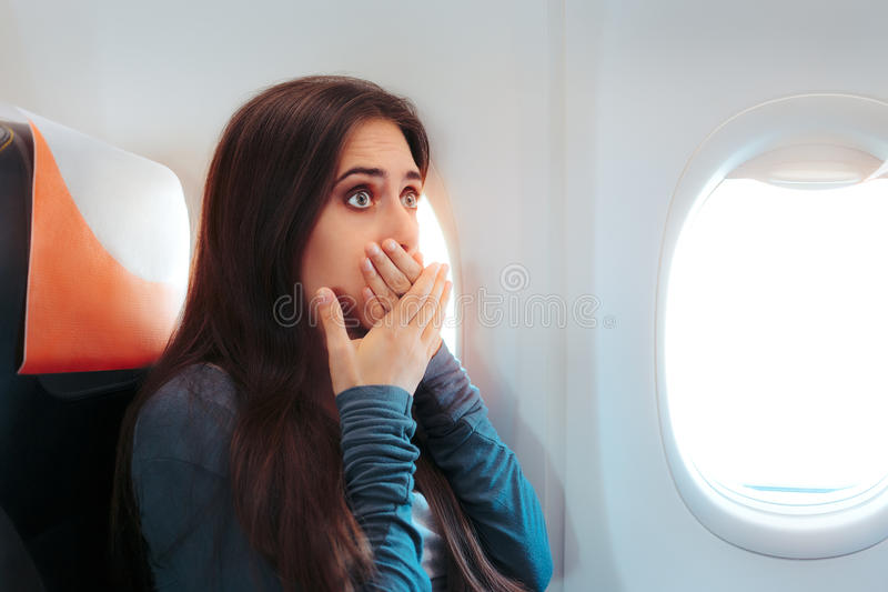 Femme s'asseyant par la fenêtre sur un avion se sentant malade images libres de droits