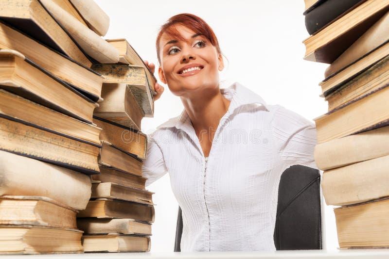 Femme s'asseyant par le bureau avec la pile des livres photo stock