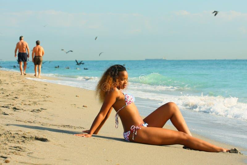 Femme s'asseyant par le rivage photographie stock