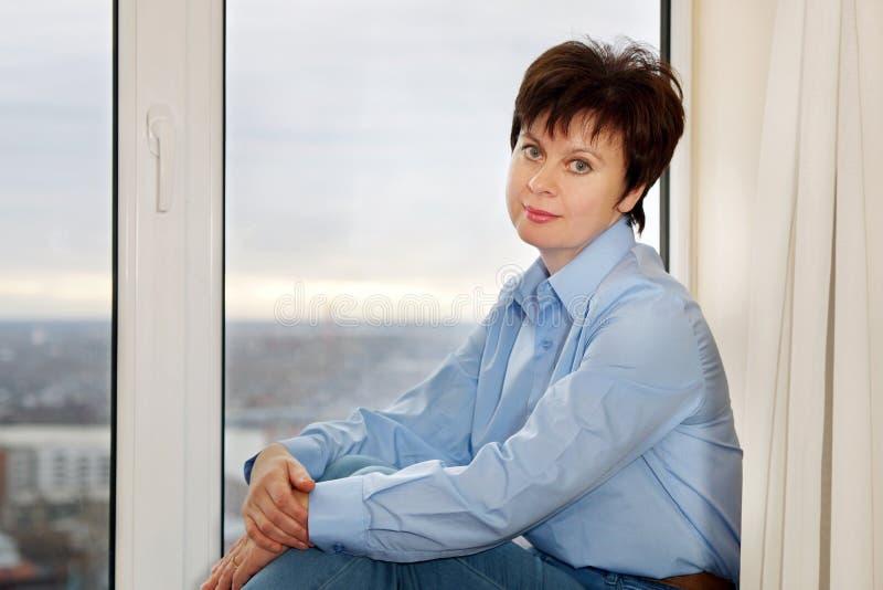 Femme s'asseyant près d'une fenêtre photo libre de droits