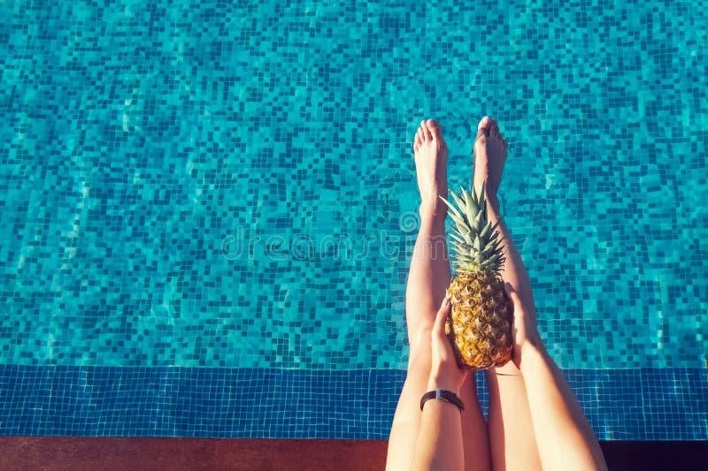 Femme s'asseyant près de la piscine et tenant l'ananas, vue à partir du dessus photos stock