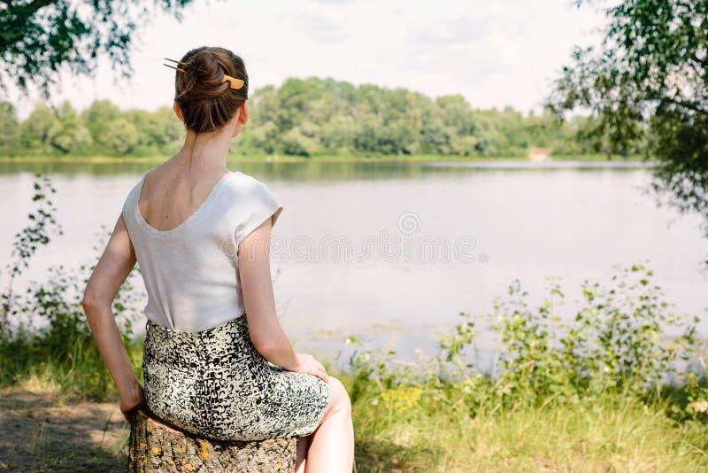 Femme s'asseyant près de la rivière photos libres de droits