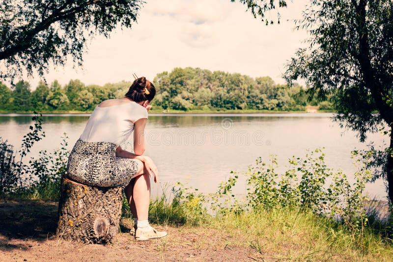 Femme s'asseyant près de la rivière image stock