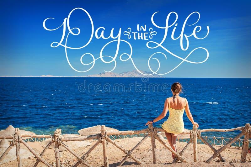 Femme s'asseyant regardant le jour de mer et de textes pendant la vie Aspiration de main de vintage de lettrage de calligraphie image stock