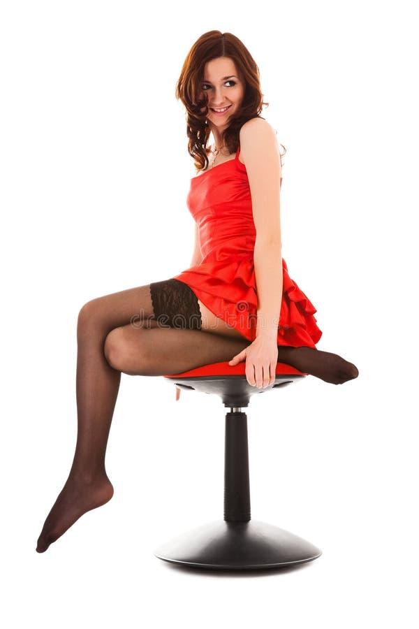 femme s'asseyant rouge de robe de présidence photographie stock libre de droits