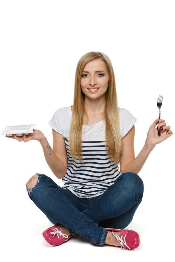 Femme s'asseyant sur l'étage et retenant la plaque et la fourchette vides photo stock
