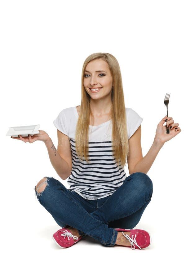 Femme s'asseyant sur l'étage et retenant la plaque et la fourchette vides images libres de droits