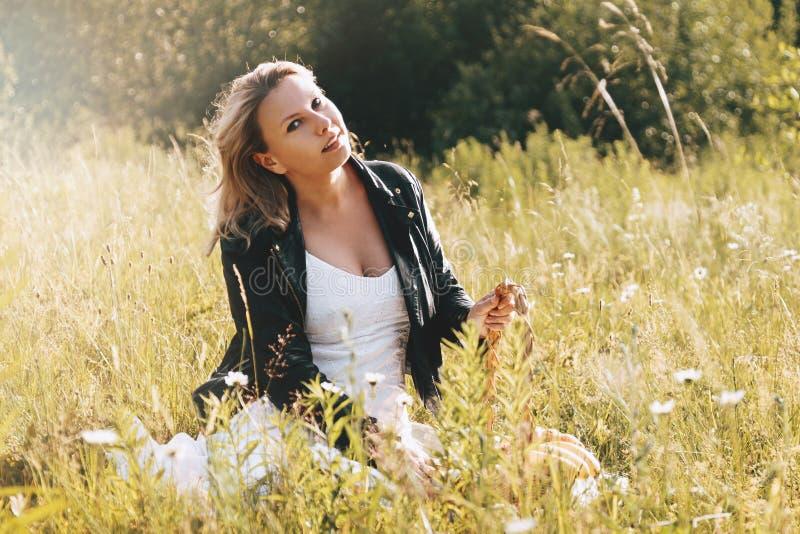 Femme s'asseyant sur l'herbe en parc image stock