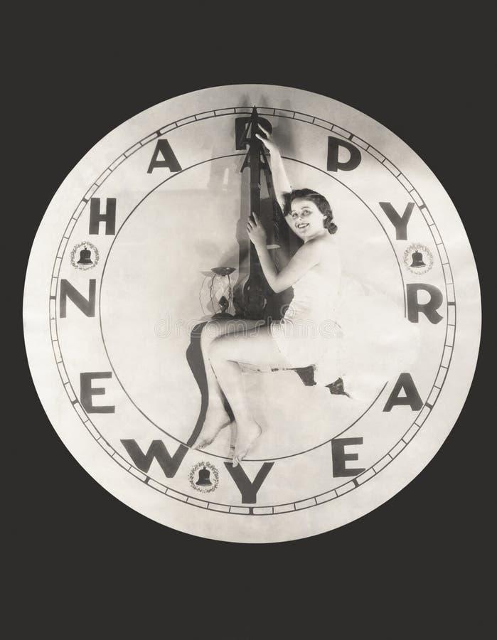 Femme s'asseyant sur l'horloge énorme de bonne année image stock