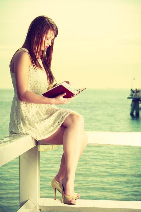 Femme s'asseyant sur l'obstacle près de la mer, livre de lecture photo stock