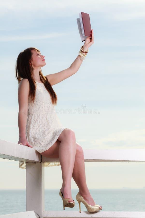 Femme s'asseyant sur l'obstacle pr?s de la mer, livre de lecture photographie stock libre de droits