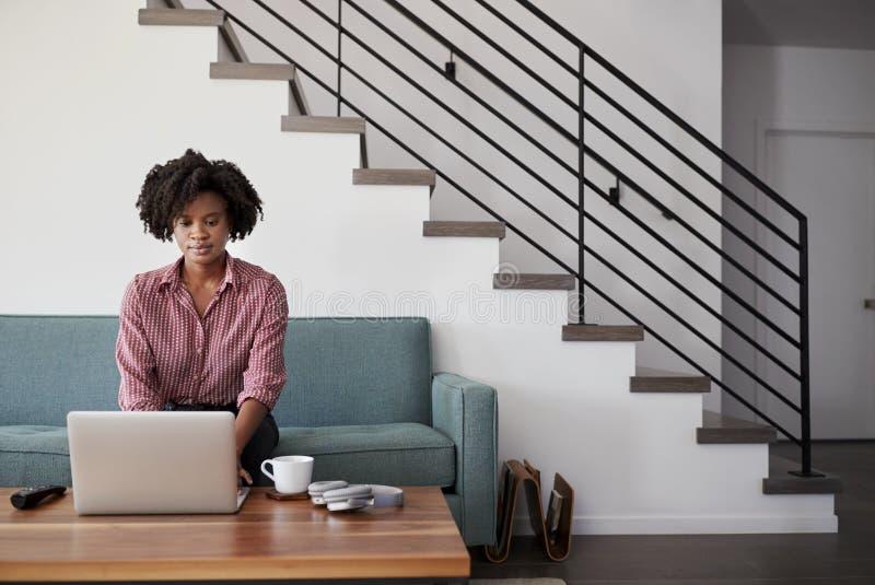 Femme s'asseyant sur l'ordinateur de Sofa At Home Using Laptop images stock