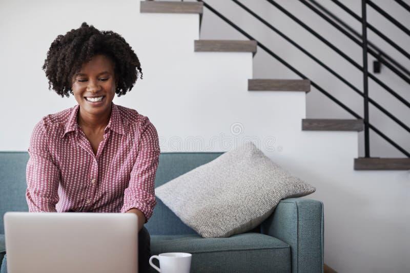 Femme s'asseyant sur l'ordinateur de Sofa At Home Using Laptop photos stock