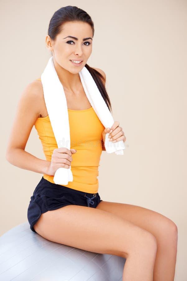 Femme s'asseyant sur la bille de forme physique photo stock