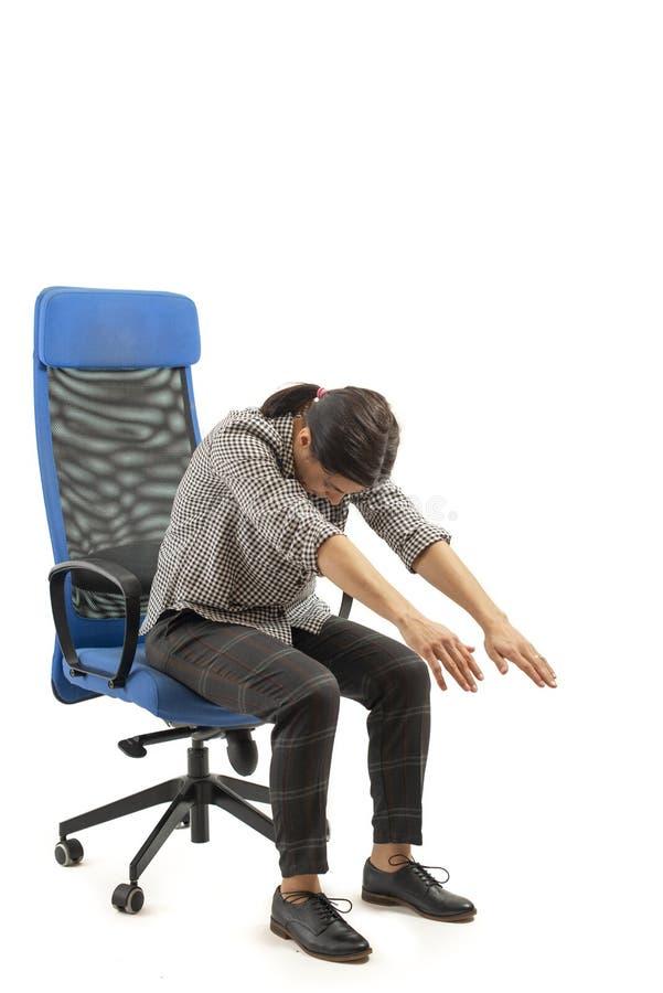 Femme s'asseyant sur la chaise de bureau et faisant étirant des mouvements image libre de droits