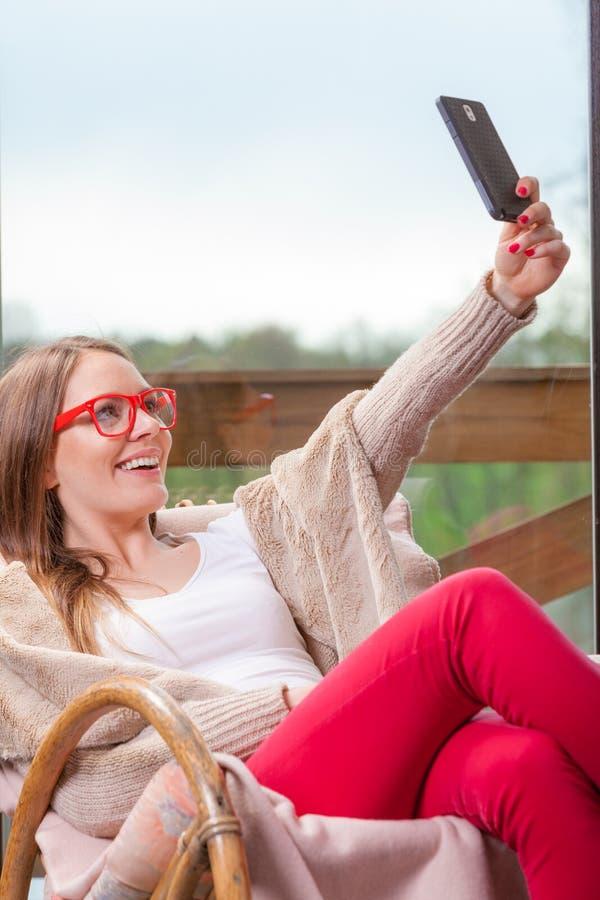 Femme s'asseyant sur la chaise faisant le selfie à la maison photographie stock libre de droits