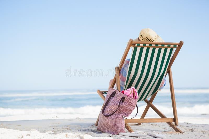 Femme s'asseyant sur la plage dans la chaise de plate-forme photos libres de droits
