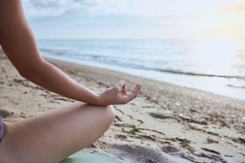 Femme s'asseyant sur la plage dans la pose de lotus et méditant, partie du corps, faisant l'exercice de yoga dehors photos stock
