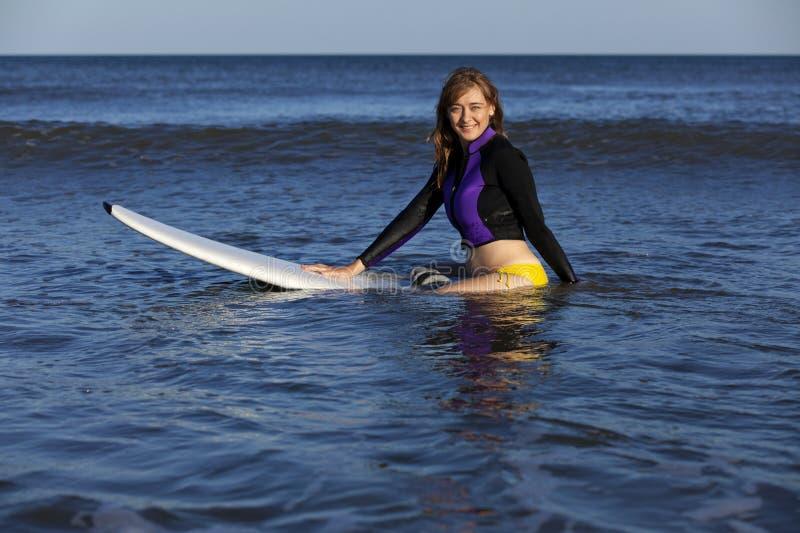 Femme s'asseyant sur la planche de surfing images libres de droits