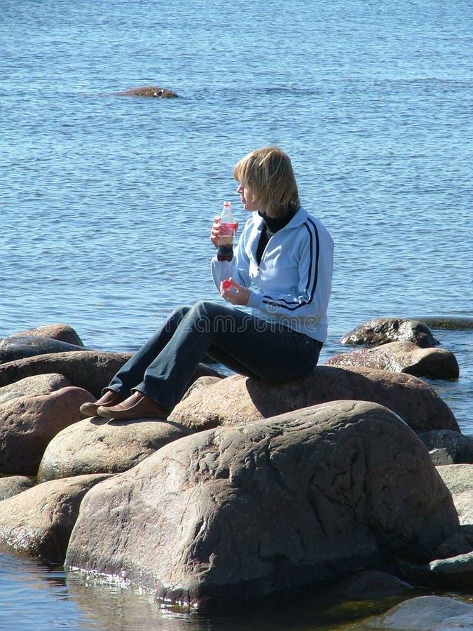 Femme s'asseyant sur la roche photo libre de droits