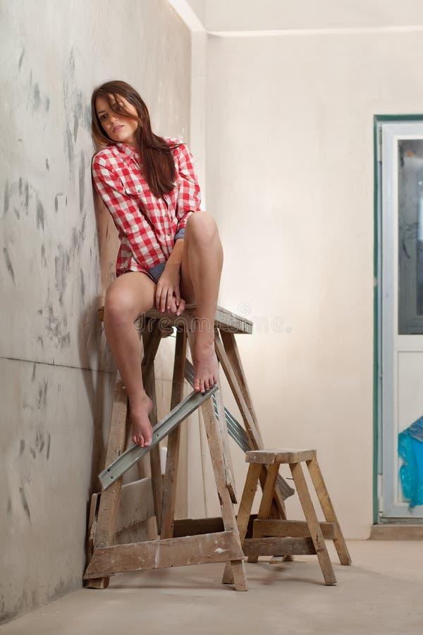Femme s'asseyant sur la table de chevalet du décorateur photos libres de droits