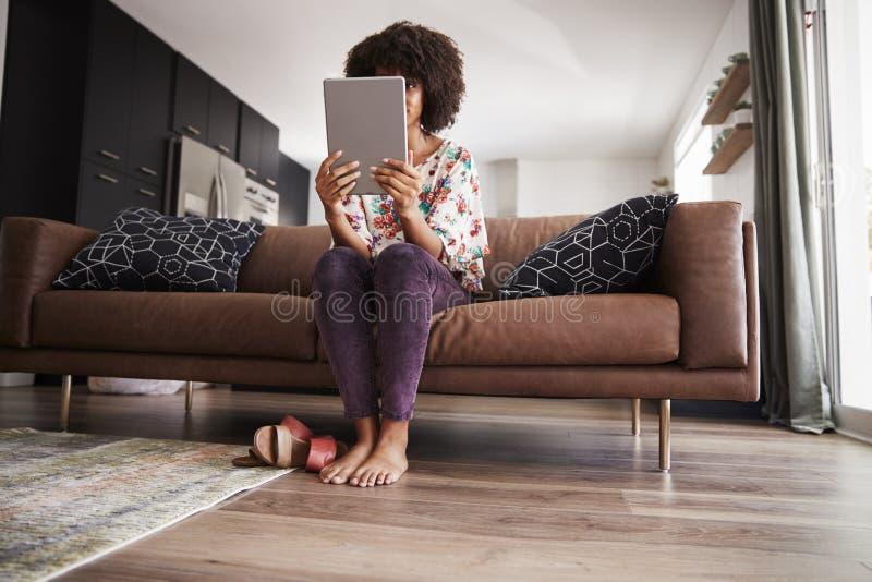 Femme s'asseyant sur la Tablette de Sofa At Home Using Digital photographie stock libre de droits