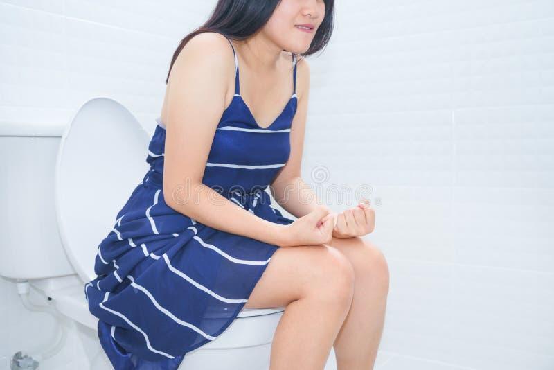 Femme s'asseyant sur la toilette avec le poing de mains - concept de constipation images stock