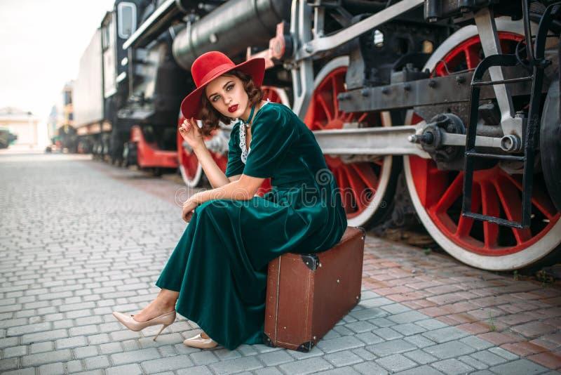Femme s'asseyant sur la valise contre le train de vapeur photos stock