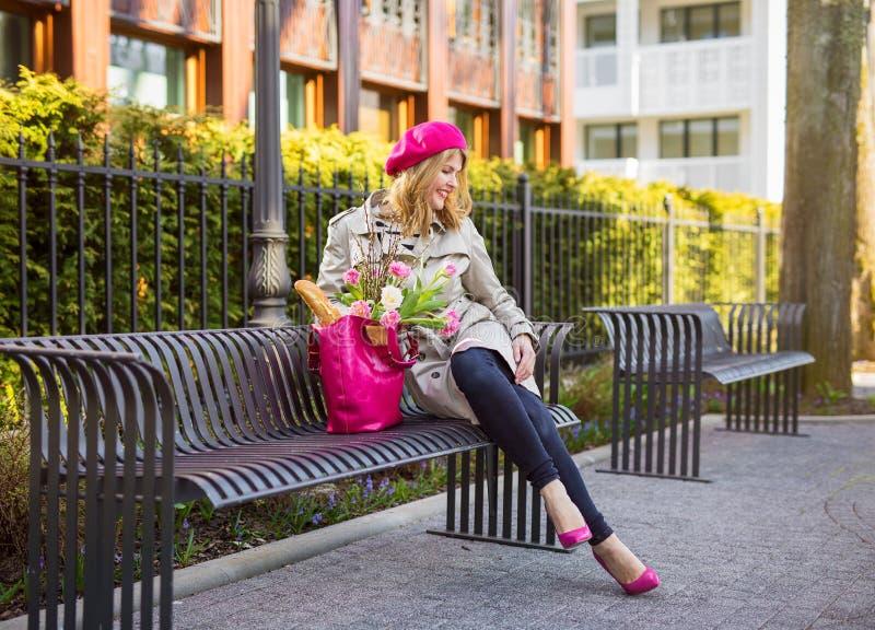 Femme s'asseyant sur le banc en parc images stock