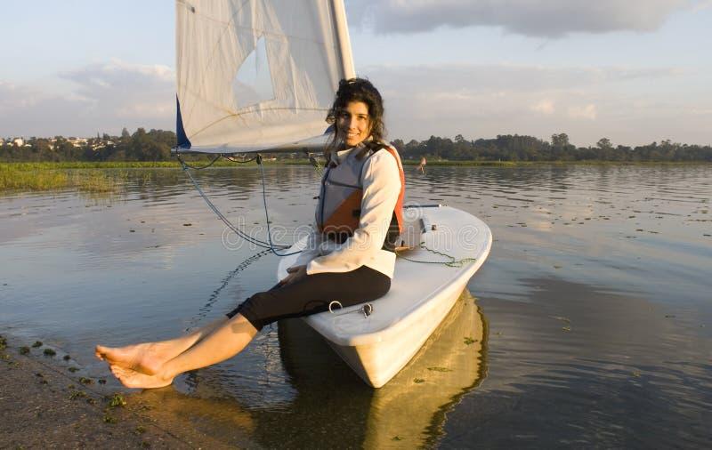 Femme s'asseyant sur le bateau à voiles dans l'eau - horizontale image libre de droits