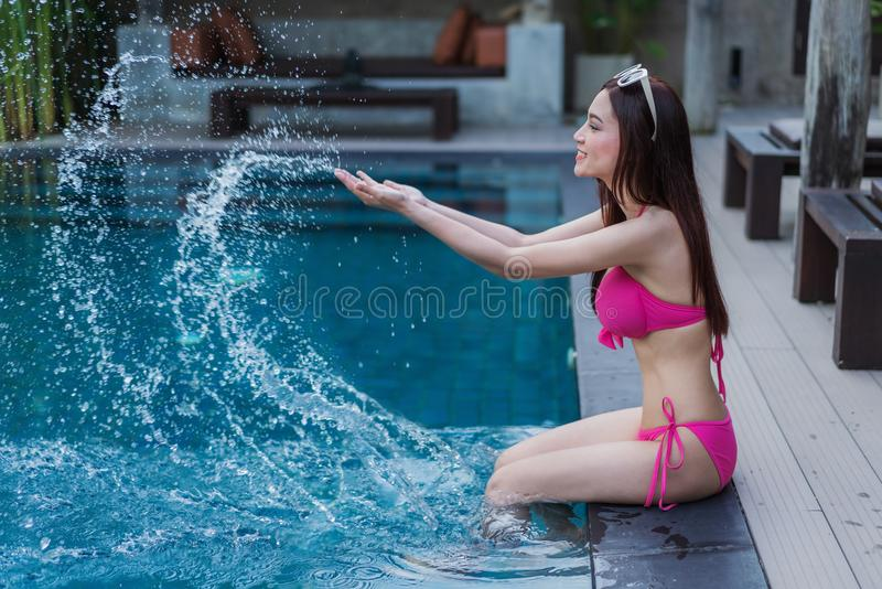 Femme s'asseyant sur le bord de la piscine et jouant l'éclaboussure de l'eau images libres de droits