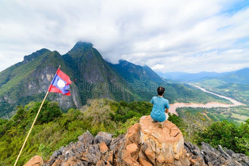 Femme s'asseyant sur le dessus de montagne à la destination de déplacement de voyage de concept de millenials de personnes mûres  photographie stock