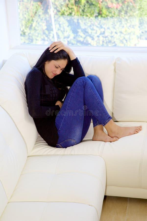 Femme s'asseyant sur le divan à la maison avec douleur de sentiment de mal d'estomac image libre de droits