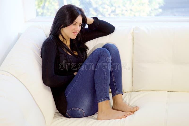 Femme s'asseyant sur le divan à la maison avec le plan rapproché de douleur de sentiment de mal d'estomac photo stock