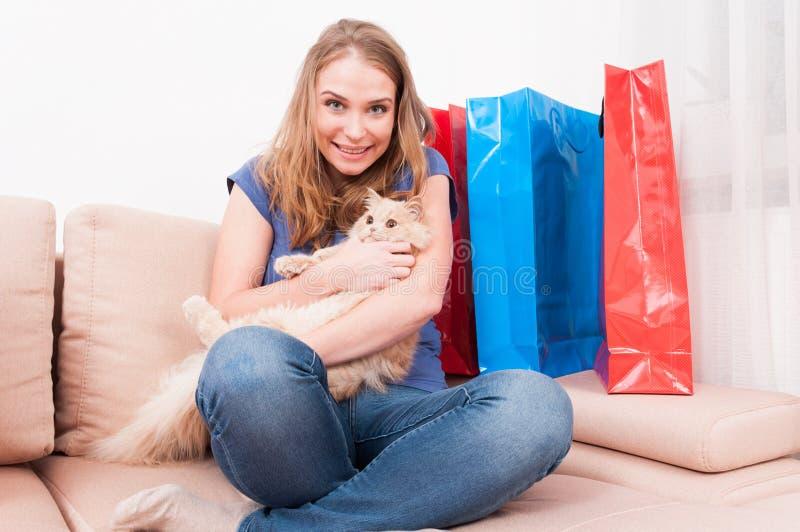 Femme s'asseyant sur le divan tenant le chat avec des paniers image libre de droits