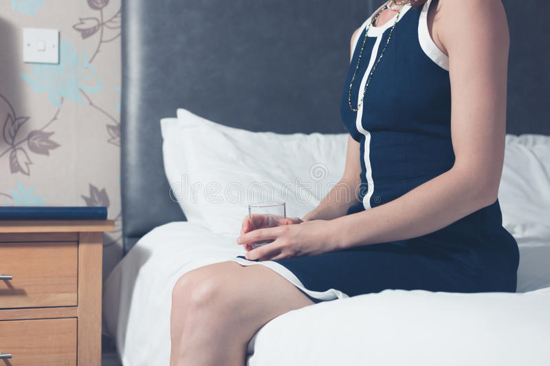 Femme s'asseyant sur le lit dans la chambre d'hôtel avec le verre dans sa main photographie stock