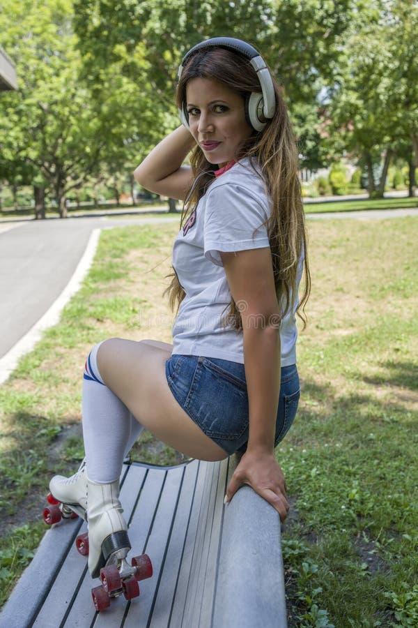 Femme s'asseyant sur le parc de banc avec des patins de rouleau photos libres de droits