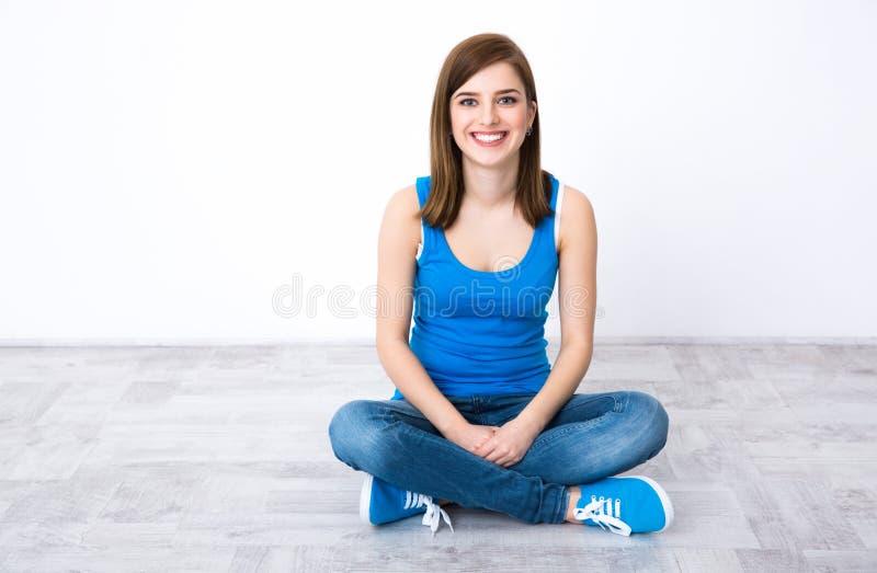 Femme s'asseyant sur le plancher en bois photographie stock