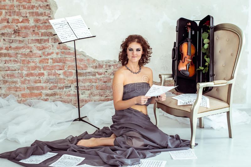 Femme s'asseyant sur le plancher près de la chaise avec le violon images libres de droits