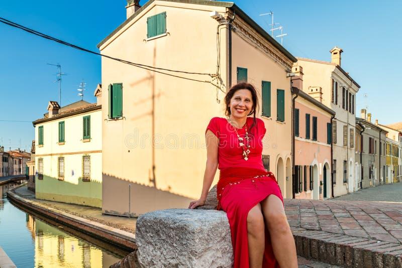 Femme s'asseyant sur le pont photos stock