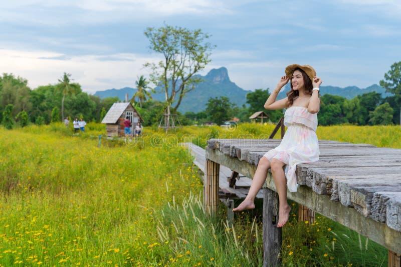 Femme s'asseyant sur le pont en bois avec le gisement de fleur jaune de cosmos photo stock