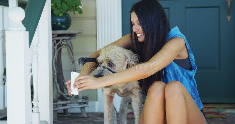 Femme s'asseyant sur le porche prenant des photos avec le chien image libre de droits