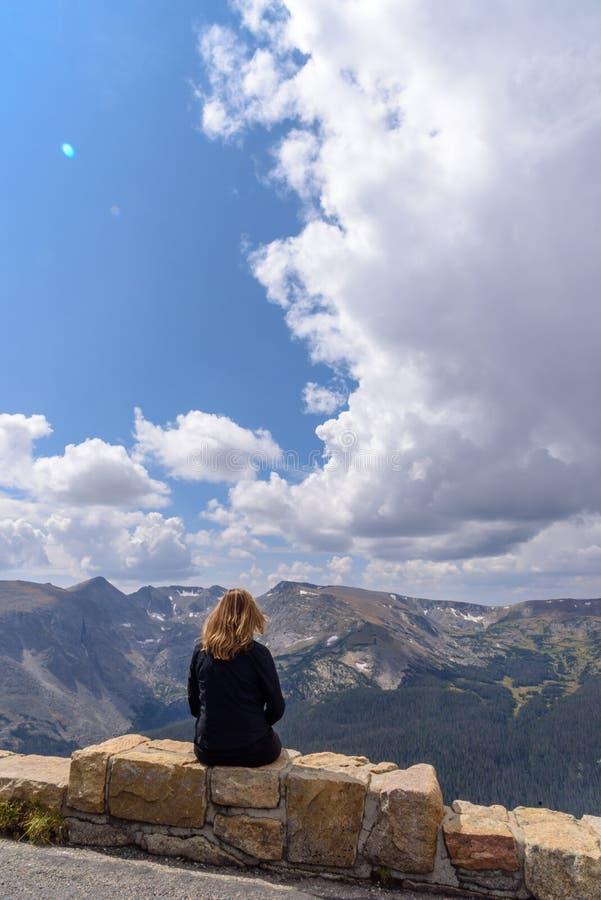 Femme s'asseyant sur le rebord regardant la gamme de montagne rocheuse photo libre de droits