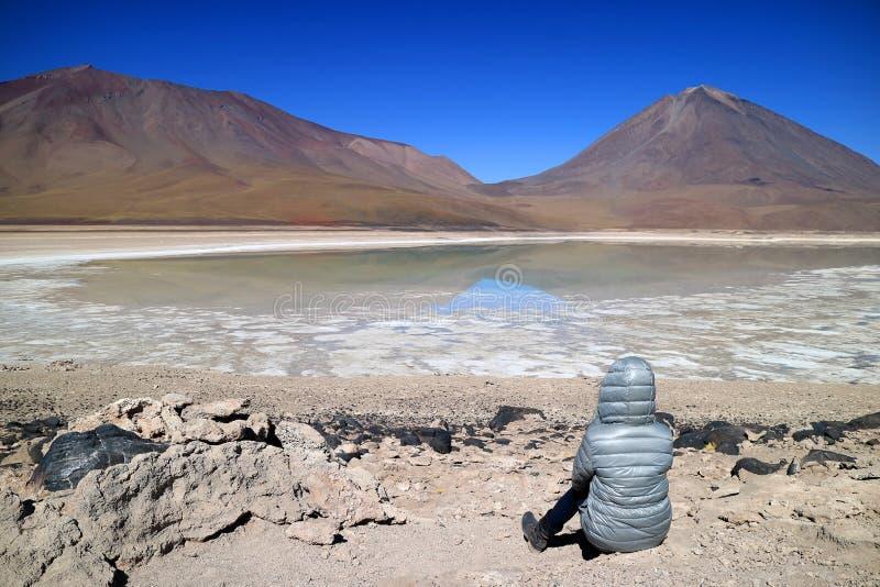 Femme s'asseyant sur le rivage attendant l'effet vert de l'eau de Laguna Verde ou le lac vert avec le volcan de Lincancabur dans  photographie stock