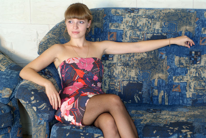 Femme s'asseyant sur le sofa images stock
