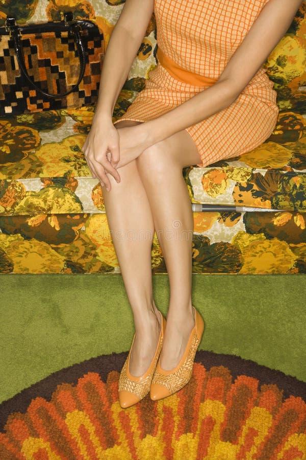 Femme s'asseyant sur le sofa. photos stock