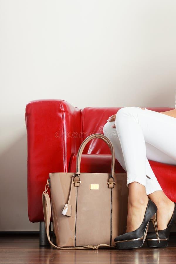 Femme s'asseyant sur le sofa présentant le sac en cuir images libres de droits