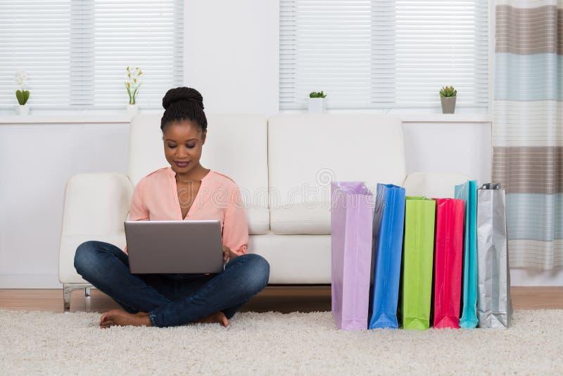 Femme s'asseyant sur le tapis faisant des emplettes en ligne photographie stock