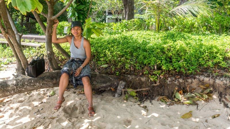 Femme s'asseyant sur le tronc d'arbre à la plage images libres de droits
