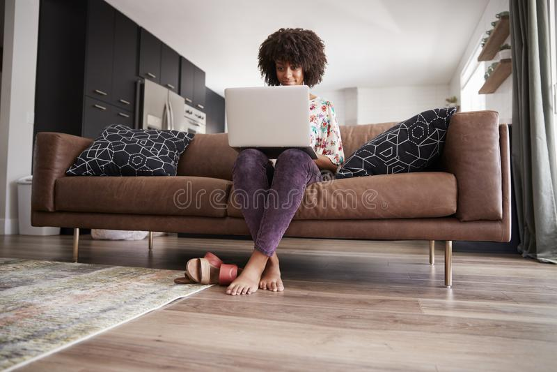 Femme s'asseyant sur Sofa At Home Using Laptop image libre de droits